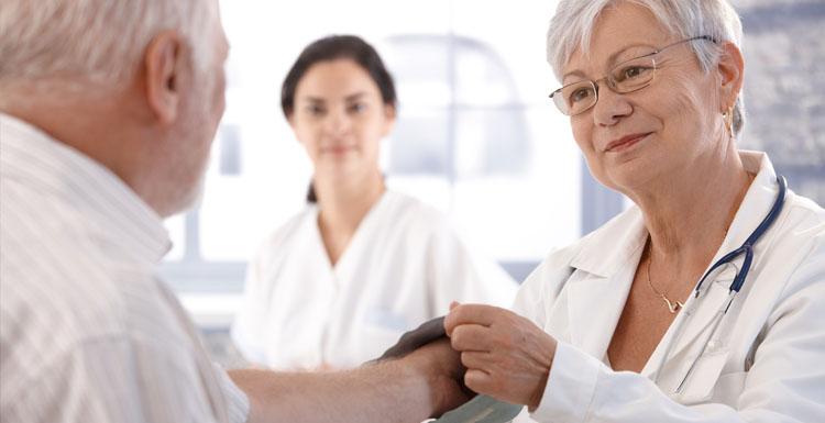 Doctor placing heart monitor on arm of elderly patient